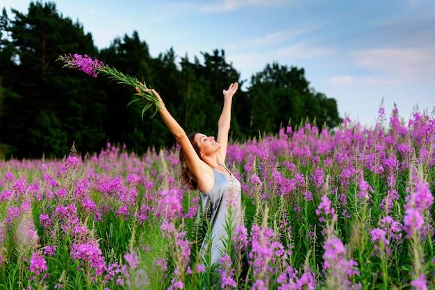 Raduje się piękna kobieta w szarej sukience z rękami w górze i bukietem kwiatów na łące fireweed