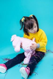 Radzenie Sobie Z Zabawkami. Jasne Małe Dziecko Z Zaburzeniami Psychicznymi, Trzymając Różową Pluszową świnkę Siedzącą Na Niebieskiej ścianie Premium Zdjęcia