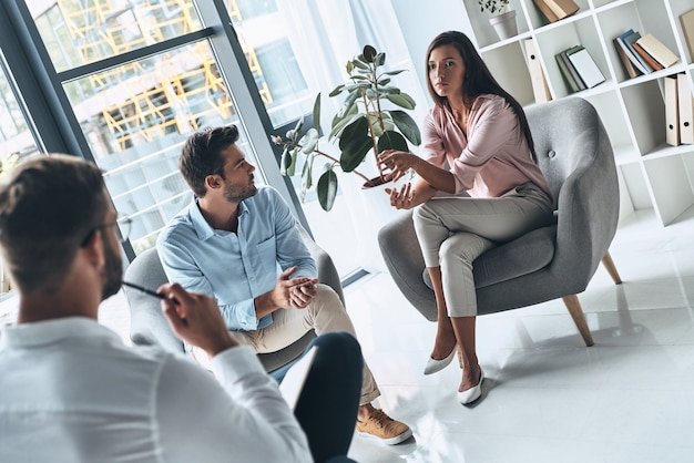 Radzenie sobie ze zdradą. młode małżeństwo rozmawia podczas sesji terapeutycznej