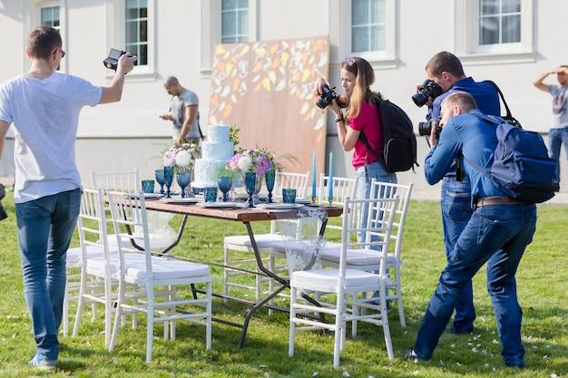 Radzivilki, białoruś - 10 października: fotografowie strzelają udekorowane na ślub elegancki stół obiadowy na warsztatach ślubnych w dniu 10 października 2016 r. w radzivilki na białorusi