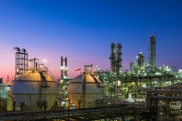 Rafineria ropy naftowej i gazu lub przemysł petrochemiczny na tle zachodu słońca na niebie, zbiornik kuli magazynowej gazu i wieża destylacyjna w przemyśle naftowym