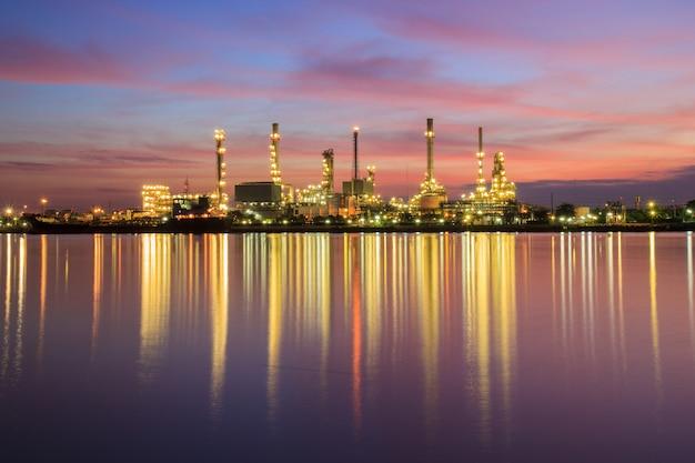 Rafineria ropy naftowej wzdłuż rzeki o zmierzchu (bangkok, tajlandia)