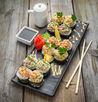 Rainbow sushi roll z łososiem, węgorzem, tuńczykiem, awokado, krewetką królewską, serek philadelphia, kawior tobica, chuka. menu sushi. japońskie jedzenie.