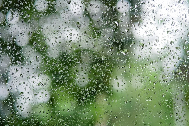 Raindrop na szklanym okno zakończeniu up używa jako tło w porze deszczowa.