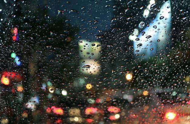 Raindrops na samochodowej przedniej szybie z zamazanym ruchu dżemem na miastowej ulicie przy nocą