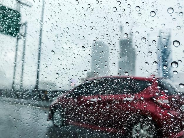 Raindrops na samochodowym szkle przy miastem w deszczowym dniu