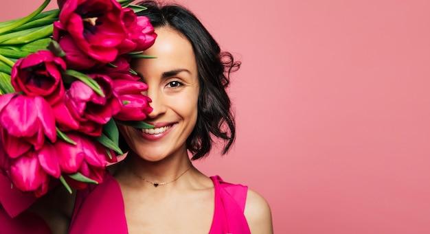 Raj dla dziewcząt. portret uroczej brunetki w różowej sukience i złotym naszyjniku, która patrzy w kamerę, zakrywając część twarzy tulipanami.
