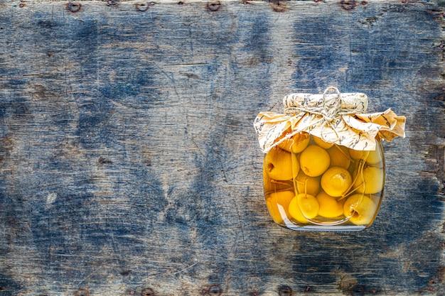Raj jabłka w syropie cukrowym na starym drewnianym tle. zbiór jesiennych zbiorów. rajski dżem jabłkowy. widok z góry. skopiuj miejsce.