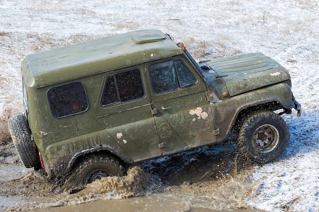 Rajd rosyjskich suv-ów w błocie zimą uwięziony pojazd terenowy wyciągnięty z rzeki