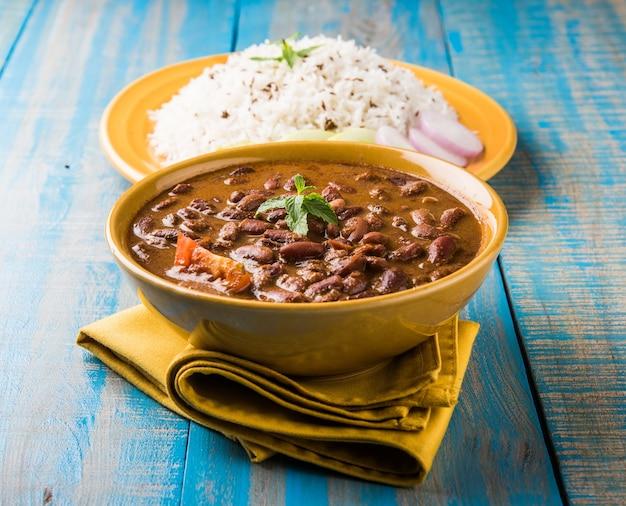 Rajma or razma to popularne północnoindyjskie jedzenie składające się z gotowanej czerwonej fasoli w gęstym sosie z przyprawami. podawane w misce z ryżem jeera i zieloną sałatą