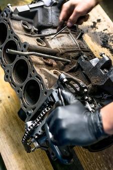 Rąk do pracy w silniku samochodowym. czyszczenie silnika samochodu. warsztat mechaniczny