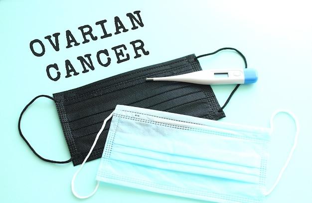 Rak jajnika napis na niebieskim tle z niebieskimi i czarnymi maseczkami medycznymi leżącymi obok.