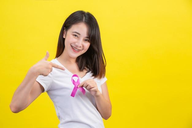 Rak piersi, kobieta w białej koszulce z satynową różową wstążką na piersi, symbol świadomości raka piersi