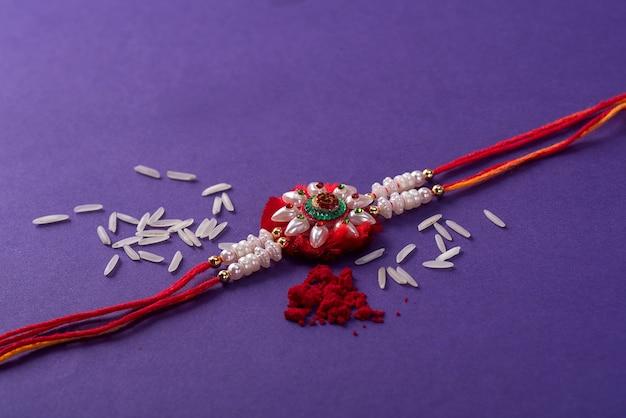 Rakhi Z Ziarnami Ryżu I Kumkum. Indyjskie świąteczne Tło Premium Zdjęcia