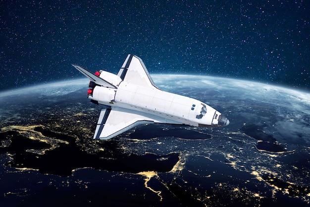 Rakieta promu kosmicznego leci nad niebieską planetą ziemię z miastami światłami na tle gwiazd. statek kosmiczny wystrzelony w kosmos rozpoczyna misję i odkrywa nowe planety