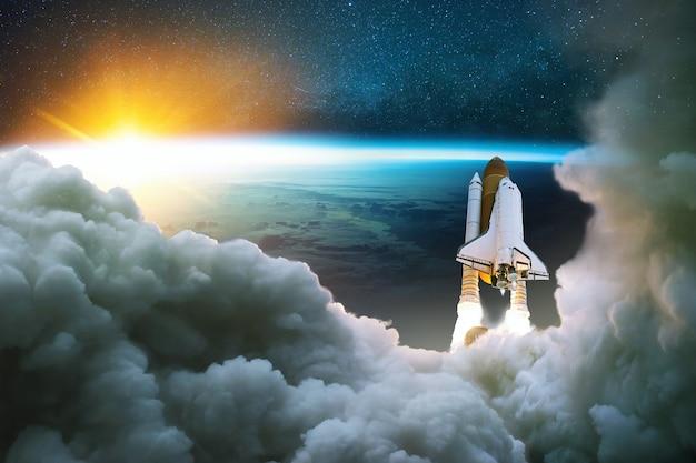 Rakieta startuje w kosmos. statek kosmiczny wystartować z podmuchem i dymem na tle niebieskiej planety ziemi i zachodu słońca. rozpocznij koncepcję misji