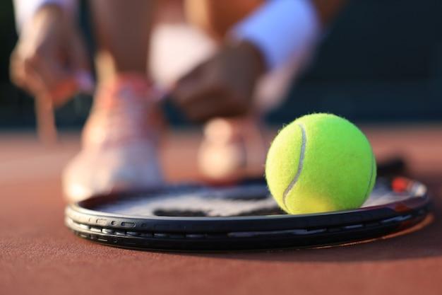 Rakieta tenisowa i piłka na korcie tenisowym.