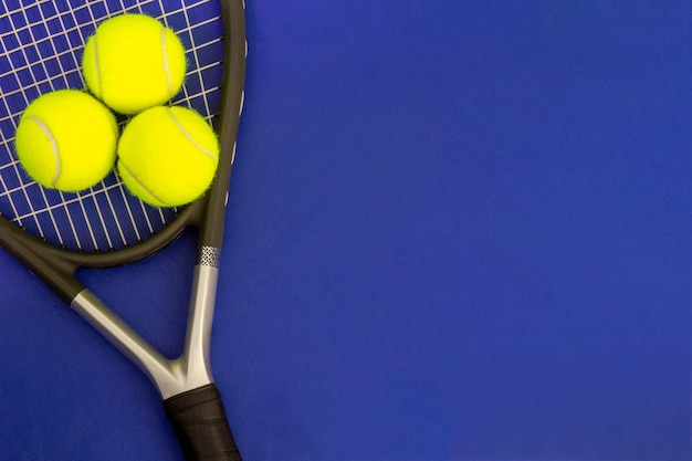 Rakieta tenisowa z piłkami tenisowymi na niebieskiej powierzchni