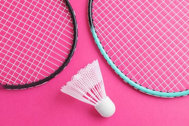 Rakiety do badmintona i wolant na jasnym różu.