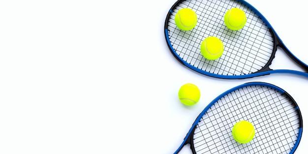 Rakiety tenisowe z kulkami na białym.