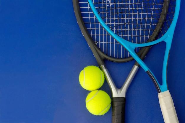 Rakiety tenisowe z piłkami tenisowymi na niebieskiej powierzchni