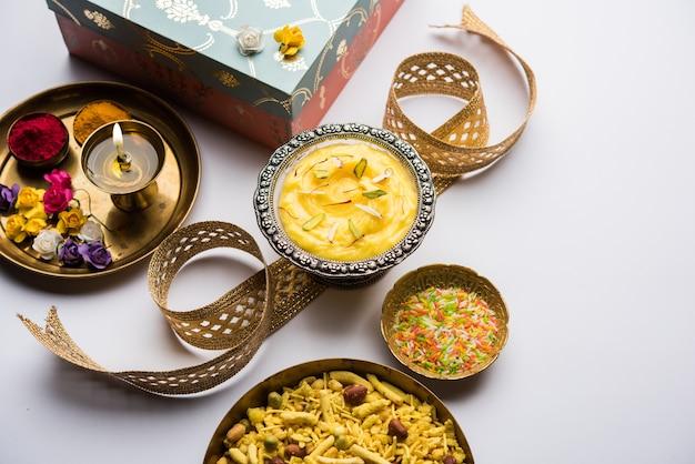 Raksha bandhan festival: konceptualny rakhi wykonany przy użyciu shrikhanda w misce z zespołem i pooja thali. tradycyjna indyjska opaska na nadgarstek będąca symbolem miłości między braćmi i siostrami