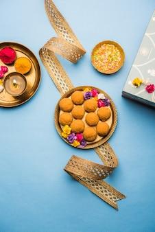 Raksha bandhan festival: konceptualny rakhi wykonany przy użyciu talerza pełnego słodkiego bundi laddu z zespołem i pooja thali. tradycyjna indyjska opaska na nadgarstek - symbol miłości między bratem a siostrą