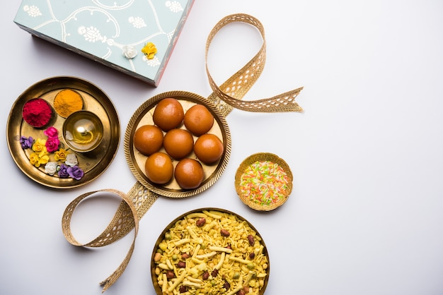 Raksha bandhan festival: konceptualny rakhi wykonany przy użyciu talerza pełnego słodyczy gulab jamun z zespołem i pooja thali.