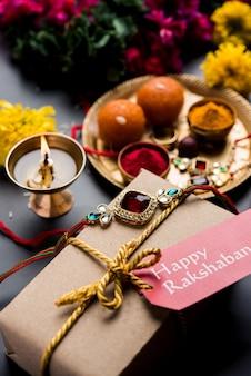 Raksha bandhan / rakshabandhan rakhi z ryżem haldi kumkum, słodki mithai, gift box, selektywne skupienie