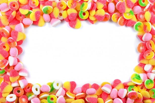 Rama asortowani gumowaci cukierki odizolowywający na bielu. widok z góry. miejsce na tekst lub projekt.