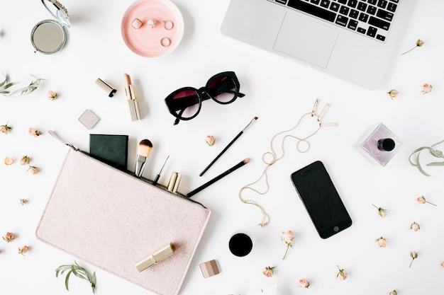 Rama biurka na biurko z widokiem z góry na płasko. kobiecy obszar roboczy na biurko z laptopem, sprzęgłem, kosmetykami, telefonem, okularami przeciwsłonecznymi, pąkami róży szminki na białym tle.