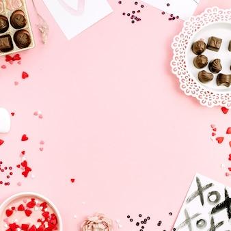 Rama cukierków czekoladowych, symboli ciepła na jasnoróżowym tle. płaski układanie, widok z góry