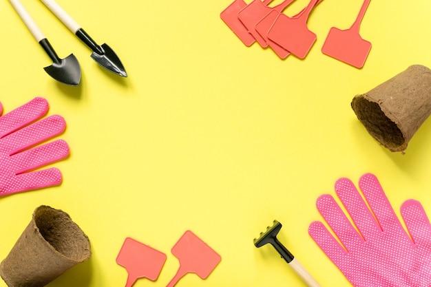 Rama dostaw ogrodniczych. narzędzia, garnki torfowe, rękawiczki i talerze do sadzonek na żółtej powierzchni, miejsce na tekst.