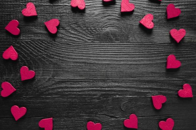 Rama fioletowych serc na czarnym drewnianym stole