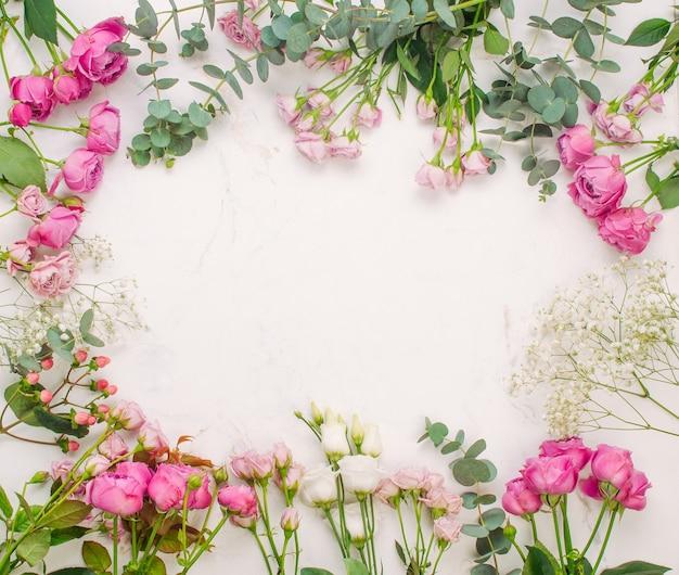 Rama kwiatów na tle białego marmuru z pustym miejscem na tekst. widok z góry, płaski układ.