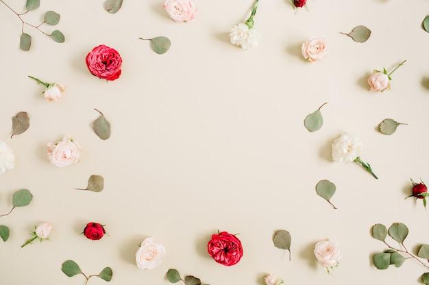 Rama kwiatów wykonana z beżowych i czerwonych róż, liść eukaliptusa na blado pastelowym beżowym tle. płaski układanie, widok z góry