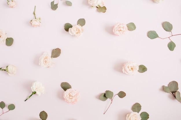 Rama kwiatów wykonana z beżowych róż, gałęzi eukaliptusa na blado pastelowym różowym tle. płaski układanie, widok z góry