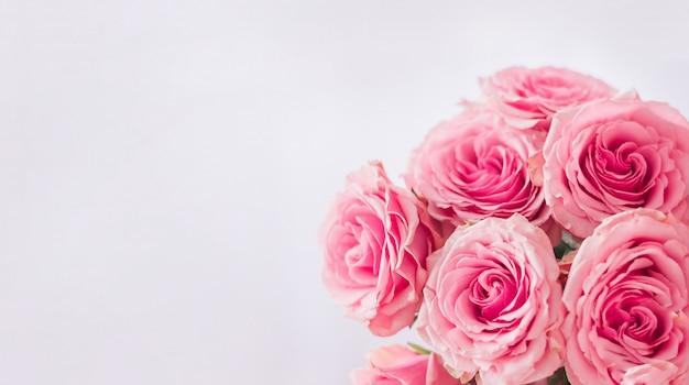 Rama kwiatowa. delikatna karta z różowymi różami na białym tle. miejsce na tekst.