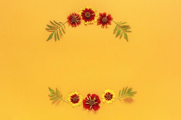 Rama kwiatowy okrągły wieniec żółtych czerwonych kwiatów na pomarańczowo