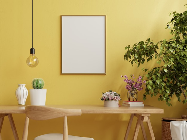 Rama na stole roboczym we wnętrzu salonu na pustej żółtej ścianie