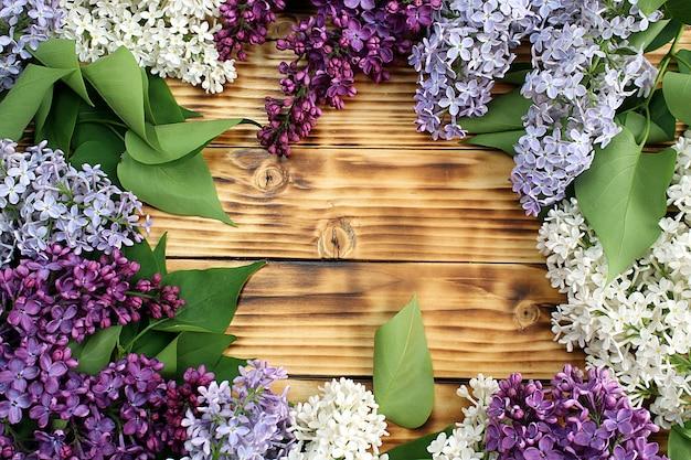 Rama na tle drewnianych ze świeżych wiosennych kwiatów bzu.