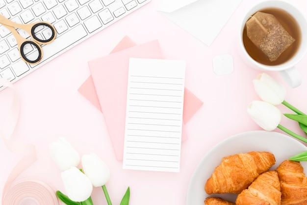 Rama narzędzi biurowych i rogalika na śniadanie