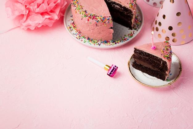 Rama o wysokim kącie z dekoracjami i różowym ciastem