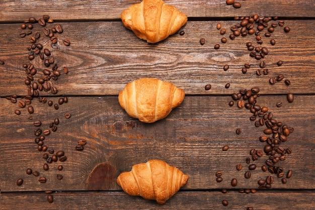 Rama palonych ziaren kawy i rogalik na drewnianym tle. zbliżenie nasion na ciemny brąz kawiarnianym stole. widok z góry.