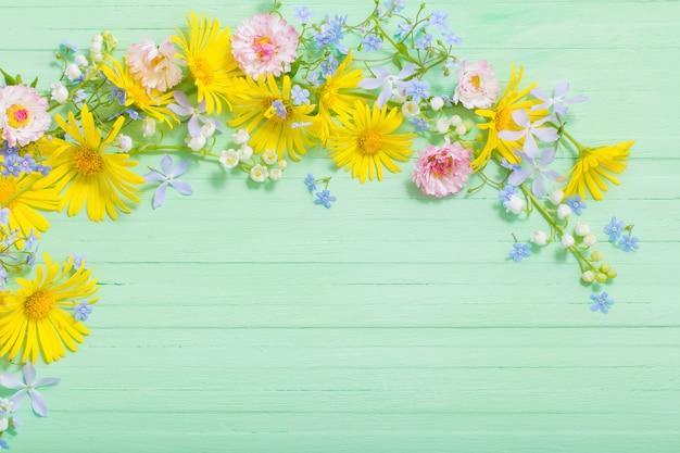 Rama piękni kwiaty na zielonym drewnianym tle