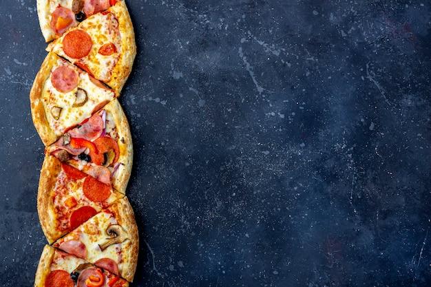 Rama plastry pizzy pepperoni z salami, pieczarkami, szynką i serem na ciemnym tle. tradycyjny włoski obiad lub kolacja. koncepcja fast food i street food. leżał płasko