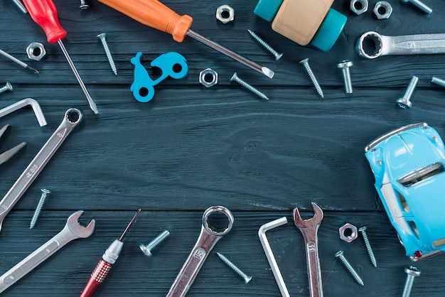 Rama różne narzędzia i zabawkarski samochód na stole