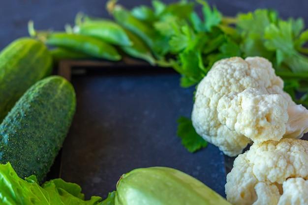 Rama różne zdrowe zielone warzywa na ciemnym stole. pojęcie właściwego odżywiania i zdrowej żywności. żywność ekologiczna i wegetariańska. widok z góry, leżał płasko, kopiować miejsca na tekst.
