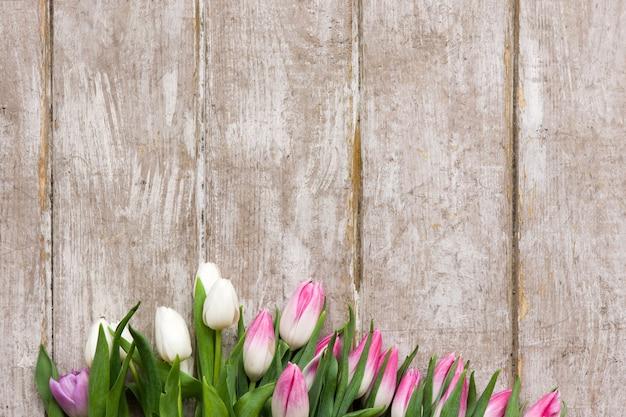 Rama różowe tulipany na drewnianym tle. bukiet kwiatów w kwiaciarni w miejscu pracy z copyspace. ślub, prezent, urodziny, 8 marca, koncepcja kartki z życzeniami na dzień matki