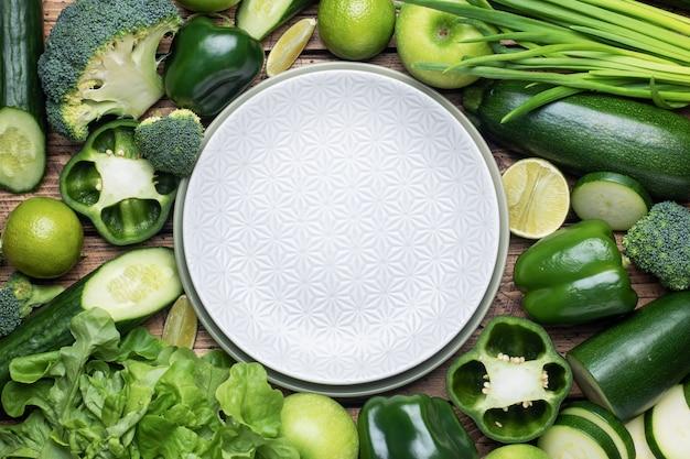 Rama świeże zielone warzywa i zioła opróżnij talerz na drewnianym tle. skopiuj miejsce